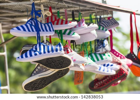 Lot of sneakers   shoes multicolored hanging on roof - stock photo