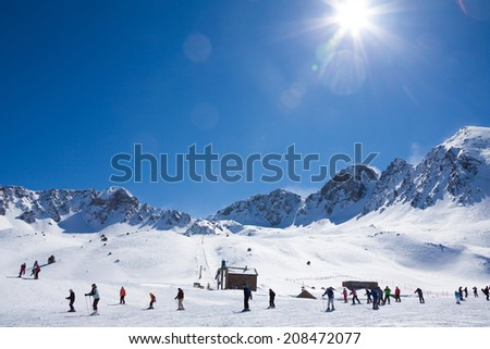 Lot's of skiers sliding down the slope with high mountain peak on the background - stock photo