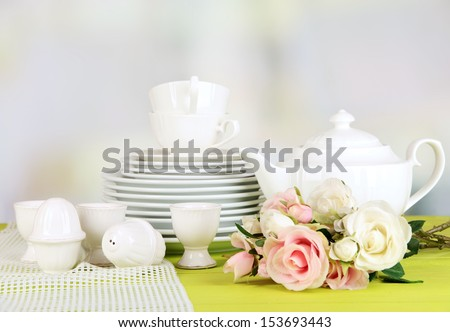 Lots beautiful dishes on wooden table on bright background - stock photo