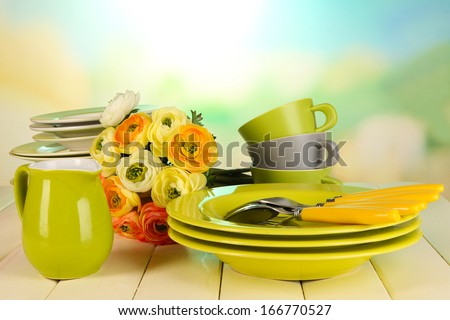 Lots beautiful dishes on wooden table on natural background - stock photo