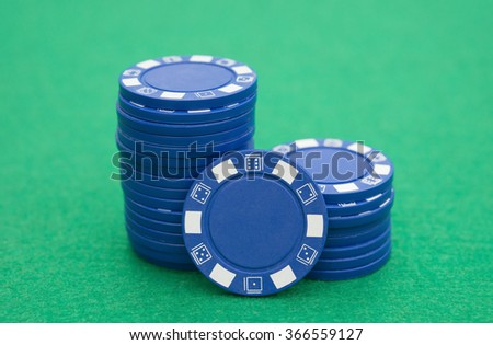 lots of blue poker chips on casino table - stock photo