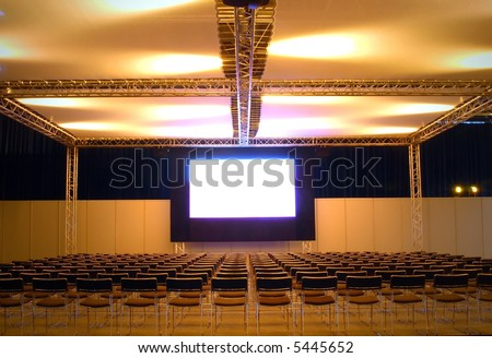 lots of chairs in front of a screen, ready for the public - stock photo
