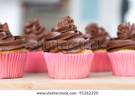 lots of chocolate frosted cupcakes in pink wrappers - stock photo
