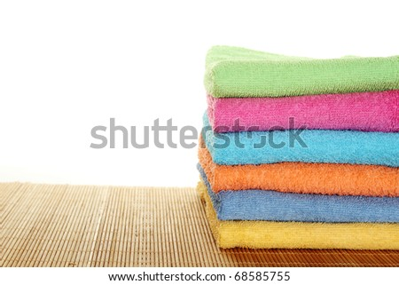 Lots of colorful bath towels stacked on each other. Isolated - stock photo