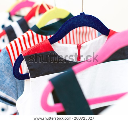 Lots of colorful dresses on hangers in shop. - stock photo