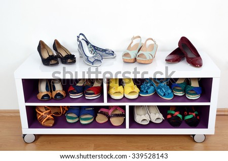 Lots of colorful summer shoes on a shelf. Shoes and sandals nicely arranged on a shelf - stock photo