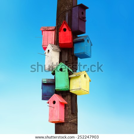 Lots of colorful wooden birdhouses on a tree against summer blue sky - stock photo