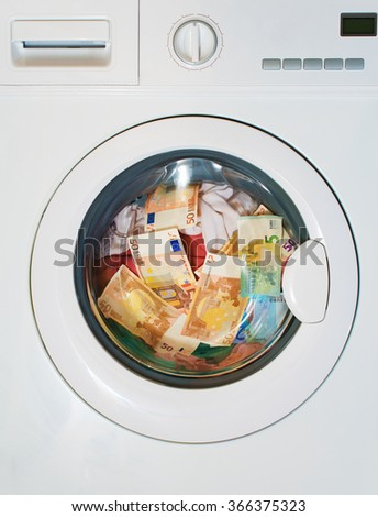 Lots of euros in washing machine. Dirty money concept. - stock photo