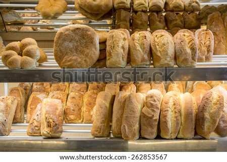 Lots of fresh bread loafs on a shelves of a bakery store - stock photo