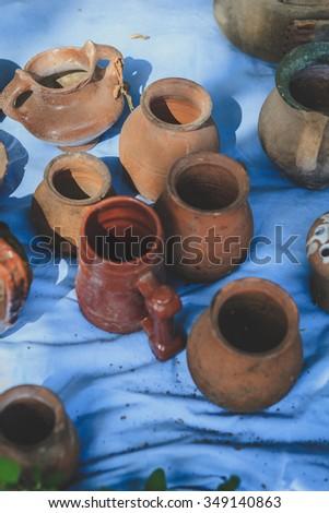 Lots of old handmade clay pots in a flea market - stock photo