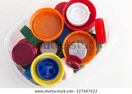 lots of plastic plugs in a plastic container isolated on white background  - stock photo