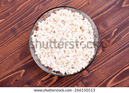 Lots of popcorn in a large, glass bowl, center table, top view - stock photo