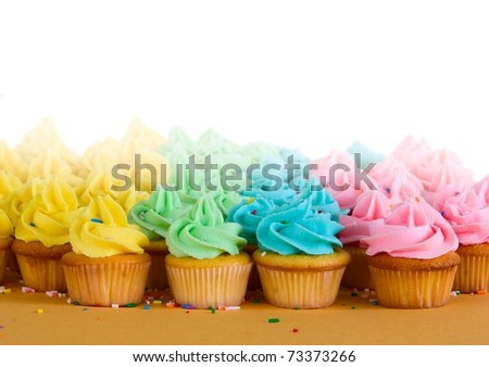 lots of rainbow cupcakes - room for copy - stock photo