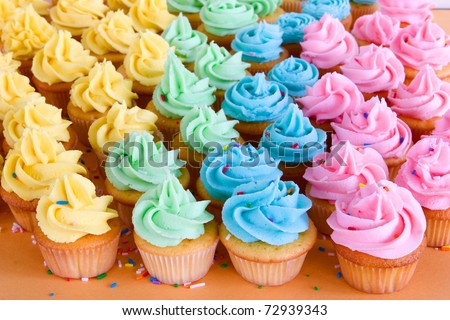 lots of rainbow cupcakes with sprinkles - stock photo