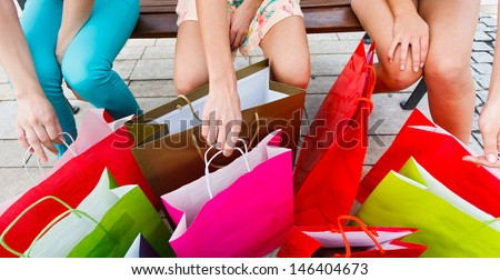 Lots of shopping bags and three girls in the city. - stock photo