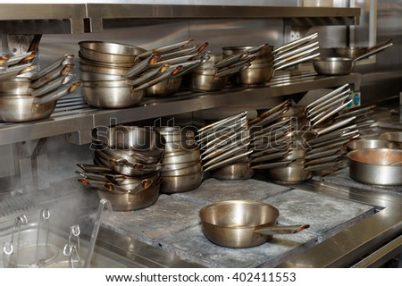 Lots of stainless steel pans, professional kitchen equipment - stock photo