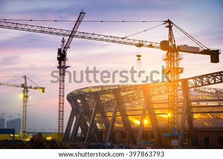 Lots of tower cranes build large residential buildings at night. - stock photo