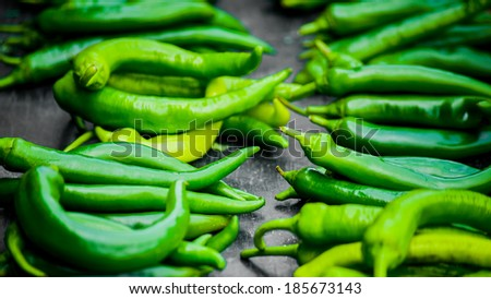 Lots of vivid acid green peppery hot pepperonies  on wooden table on the marketplace - stock photo