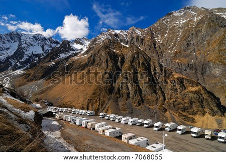 Lots of white caravans in front of the Pyrenees mountains in France - stock photo