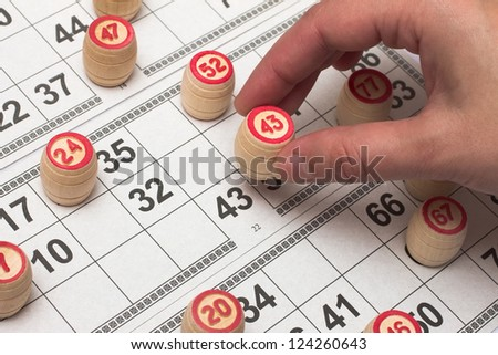 Lotto cards and female hand holding a wooden keg. - stock photo