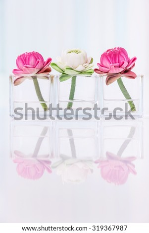 Lotus flower or water lily decoration in glass vase on table, Buddhism and zen meditation concept - stock photo