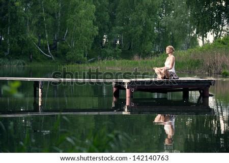 Lotus position on the lake - stock photo