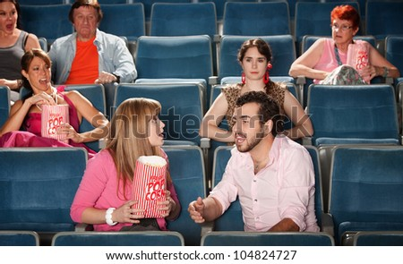 Loud couple talking with annoyed people in crowded theater - stock photo