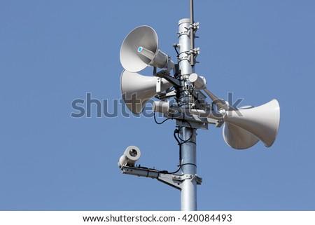 loudspeaker of disaster-forecast against clear blue sky - stock photo