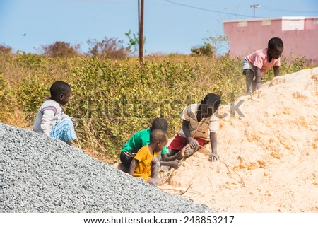 LOUGA, SENEGAL - MAR 15, 2013: Unidentified Senegalese children play on the sand hill. People in Senegal suffer of poverty due to the unstable economic situation - stock photo