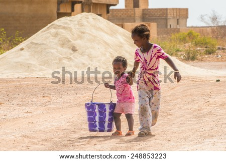 LOUGA, SENEGAL - MAR 15, 2013: Unidentified Senegalese two sisters walk over the sand. Children in Senegal suffer of poverty due to the unstable economic situation - stock photo