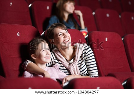 Loughing mother and daughter at the cinema watching a movie - stock photo