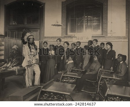 Louis Firetail, wearing Sioux tribal clothing, in an American history class at Hampton Institute. Founded as an African American college during the Civil War. Ca. 1900. - stock photo