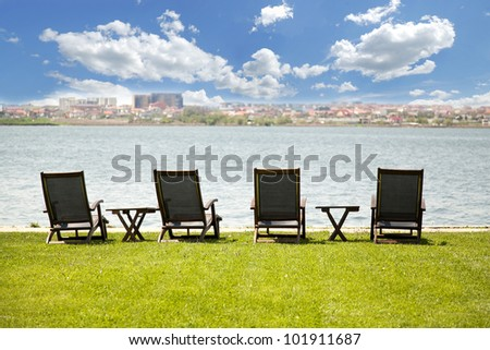 lounge chair on green grass near the lake - stock photo
