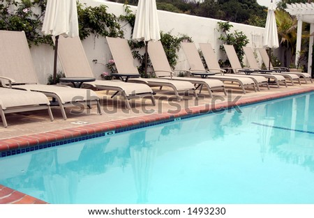 Lounge chairs by the pool. - stock photo
