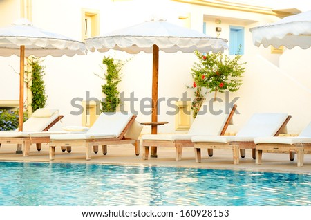 lounge chairs by the pool at sunset time.  Light Mediterranean-style bungalows - stock photo