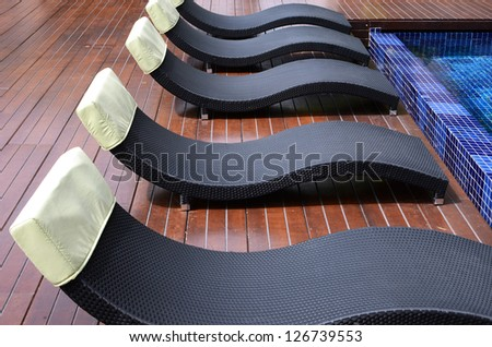 lounge chairs by the swimming pool - stock photo
