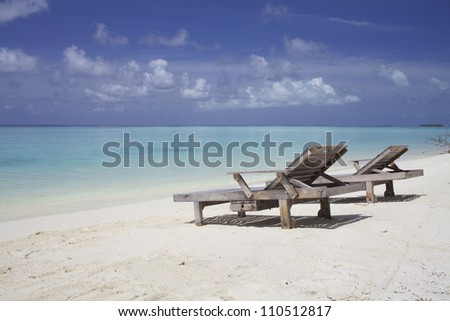 Lounge chairs on tropical island beach with blue water and white sand - stock photo