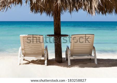 Lounge chairs under sunshade at tranquil beach - stock photo
