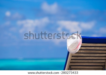 Lounge chairs with hat on tropical white beach - stock photo