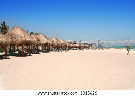 lounge chairs with thatch cover on the beach..space for writing - stock photo