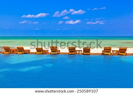 Loungers and pool on Maldives beach - nature vacation background - stock photo