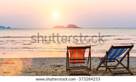 Loungers at the seaside at sunset. - stock photo