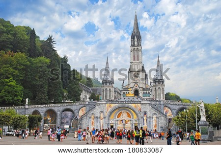 LOURDES - AUGUST 23: Christian cross on a background the Basilica of our Lady of the Rosary  in Lourdes, France on August 23, 2011. - stock photo