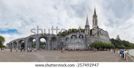 LOURDES, FRANCE - JULY 23, 2014: Tourists and Pilgrims visiting the Sanctuary of Our Lady of Lourdes. Lourdes is able to take in some 5,000,000 pilgrims and tourists every season. - stock photo
