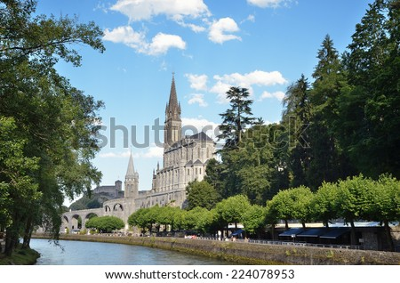Lourdes is a major place of Roman Catholic pilgrimage. The Basilica of Our Lady of Immaculate Conception (Upper church) is built on the top of the rock above the Grotto near the fast-flowing river. - stock photo