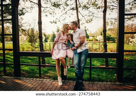 Love and children. Young couple kissing while their daughter hiding her face - stock photo