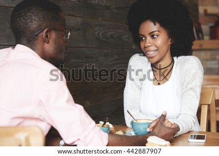 Love and friendship concept. Beautiful African young people having a first date at a restaurant, drinking coffee and eating dessert, looking at each other with affection, sitting at the wooden table - stock photo