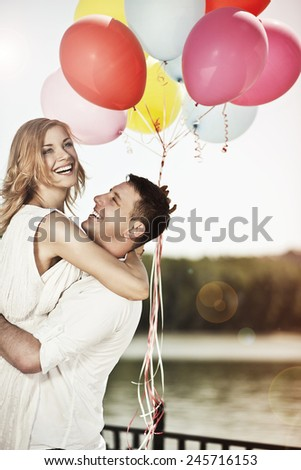 Love and holiday concept. Young happy couple holding colorful ballons and embracing. - stock photo