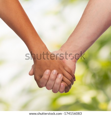 love and relationships concept - closeup of woman and man holding hands - stock photo