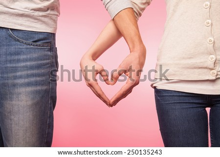 love and relationships concept -  woman and man hands showing heart shape - stock photo